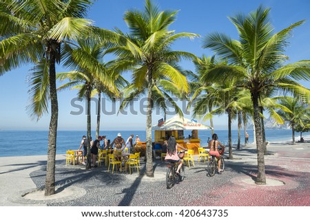 RIO DE JANEIRO - APRIL 4, 2016: Residents on bicycles ride past a kiosk selling drinks and coconuts standing amongst palm trees at the Arpoador end of Ipanema Beach.
