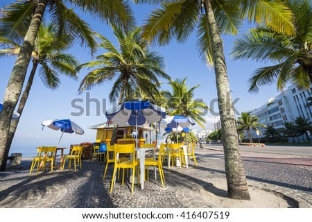 RIO DE JANEIRO - APRIL 4, 2016: Typical beach kiosk selling drinks and coconuts sits among palm trees at the Arpoador end of Ipanema Beach.