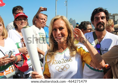 RIO DE JANEIRO, AUGUST 5, 2016: Olympic torch arrives in Ipanema beach for the Olympic Games. The girl from Ipanema Helo Pinheiro holds the torch.
