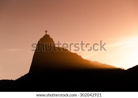 Rio de Janeiro, Brazil - April 4, 2015: The famous Rio de Janeiro landmark - Christ the Redeemer statue and Corcovado mountain silhouette by sunset. - stock photo