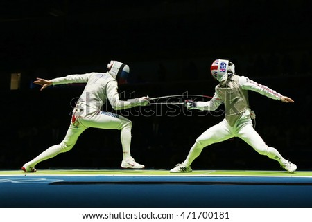 RIO DE JANEIRO, BRAZIL - AUGUST 12, 2016: Russian fencer (L) attacks Great Britain fencer at the Men's team foil quarterfinal of the Rio 2016 Olympic Games at the Carioca Arena 3