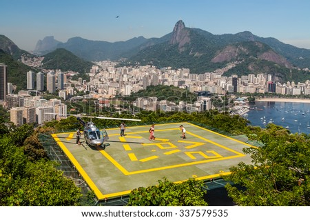 RIO DE JANEIRO, BRAZIL - DECEMBER 21, 2012: Tourists enjoying the Helicopter aerial tour from Sugarloaf Mountain in Rio de Janeiro, Brazil. - stock photo