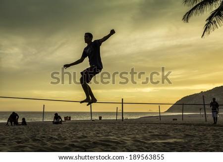 RIO DE JANEIRO, BRAZIL - FEBRUARY 24, 2014: Boy practices slacklining at Ipanema Beach in Rio de Janeiro during sunset. It is very popular sport on Ipanema Beach. - stock photo