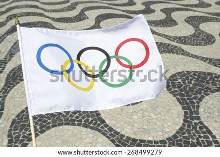 RIO DE JANEIRO, BRAZIL - FEBRUARY 23, 2015: Olympic flag waves in front of the iconic wave pattern of the sidewalk on Copacabana Beach. - stock photo