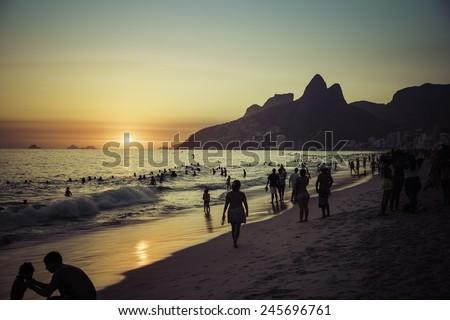 RIO DE JANEIRO, BRAZIL - JANUARY 2015: People relaxing on Ipanema Beach during beautiful hot summer sunset. - stock photo