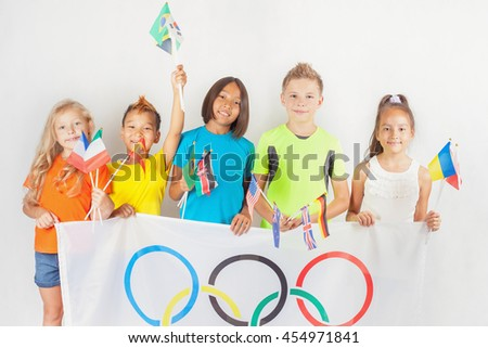 RIO DE JANEIRO, BRAZIL - JULY 17, 2016: Group of children holding a flag of five rings symbol of Olympic Games and international flags. Rio de Janeiro 2016 Brazil. Happy fans watching tv. Volunteer.