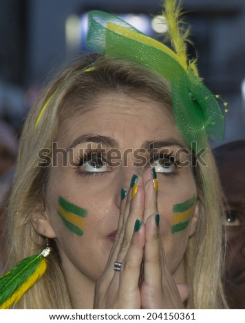 Rio de Janeiro, Brazil - JULY 08, 2014: Soccer fan of Brazil reacts after Brazil defeated by Germany during the World Cup Semi-finals game at the Fan Fest in the Copacabana beach. NO USE IN BRAZIL.