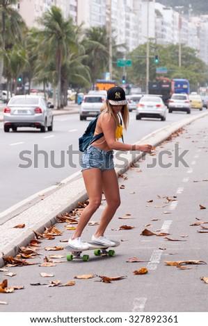 RIO DE JANEIRO, BRAZIL - JULY 27, 2015: Unidentifien woman rides a skateboard down the bicycle road. - stock photo