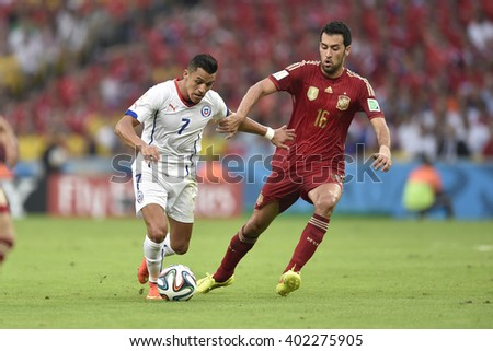 RIO DE JANEIRO, BRAZIL - June 18, 2014: Alexis SANCHEZ of Chile and Sergio BUSQUETS of Spain during the FIFA 2014 World Cup. Spain is facing Chile in the Group B at Maracana Stadium - stock photo