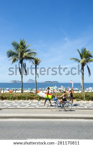 RIO DE JANEIRO, BRAZIL - MARCH 08, 2015: Brazilians walk and ride bicycles with surfboards on the beachfront boardwalk at Ipanema Beach.  - stock photo