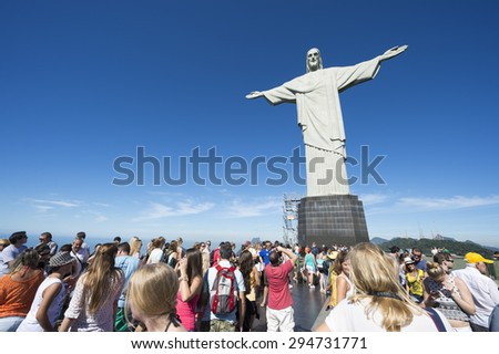 RIO DE JANEIRO, BRAZIL - MARCH 05, 2015: Groups of tourists pose for pictures on a bright morning at the viewing platform of the statue of Christ the Redeemer, at the peak of Corcovado Mountain. - stock photo