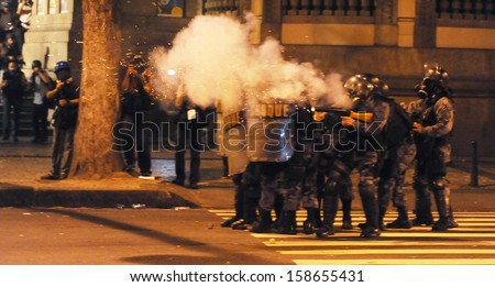 RIO DE JANEIRO, BRAZIL - OCTOBER 15: Anti- riot police battalion fire pepper gas bombs against demonstrators along the city center main avenue, Rio Branco, during a protest in support the teacher's strike as the annual October 15 Teachers' Day holiday cam - stock photo