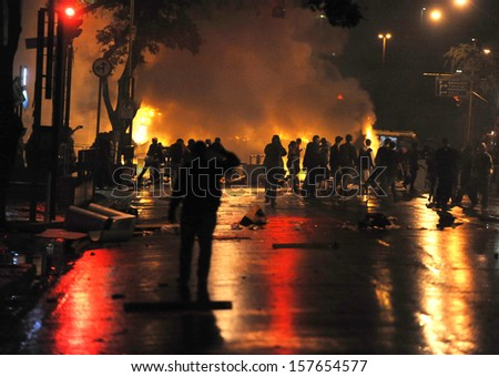 RIO DE JANEIRO, BRAZIL - OCTOBER 08: Black Bloc protesters look at burned buses in Rio de Janeiro's main avenue during schoolteachers demonstrations demanding better wages on October 8th, 2013 in Rio de Janeiro, Brazil.