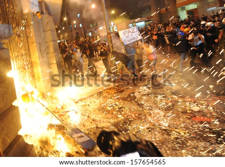 RIO DE JANEIRO, BRAZIL - OCTOBER 08: Black Bloc protesters throw molotov cocktails against the Chamber of Counselors municipal building during schoolteachers demonstrations demanding better wages on October 8th, 2013 in Rio de Janeiro, Brazil. - stock photo