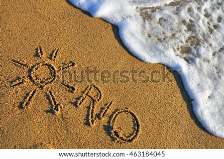 Rio de Janeiro hand made sign with sun and waves on the sand beach. Summer background