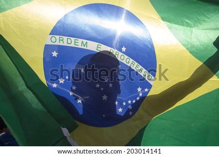Rio de Janeiro - July 4, 2014:FAN FEST- Brazil versus Colombia, a Brazilian soccer fan holds the national flag as he attends the match, Brazil versus Colombia at the FIFA Fan Fest in Copacabana, Brazil. No use in Brazil.