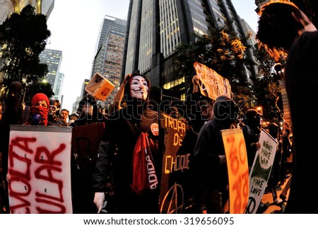 Rio de Janeiro - July 11, 2013: Protester wearing Anonymous mask takes part in a manifestation against public transport fares, social exclusion, corruption and police violence. - stock photo