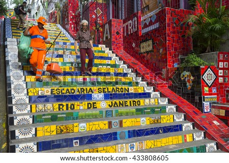 RIO DE JANEIRO - MARCH 29, 2016: A municipal COMLURB worker sweeps the colorful mosaic tiled staircase of the Escadaria Selarón  (Selaron Steps) before the arrival of tourists at the popular landmark. - stock photo