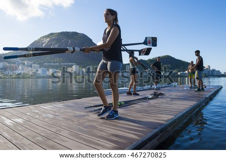 RIO DE JANEIRO - MARCH 22, 2016: After training, a female Brazilian rower carries oars back to the clubhouse at Lagoa Rodrigo de Freitas Lagoon, a venue for the Rio 2016 Olympic Games.