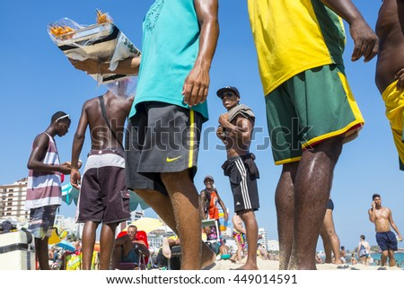 RIO DE JANEIRO - MARCH 05, 2013: Brazilian vendors congregate as they sell drinks and snacks to sunbathers on Ipanema Beach. - stock photo