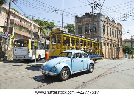 RIO DE JANEIRO - MARCH 28, 2016: Classic blue Volkswagen Fusca Beetle passes an iconic bonde tram near Largo dos Guimarães, the heart of the hillside neighborhood of Santa Teresa.