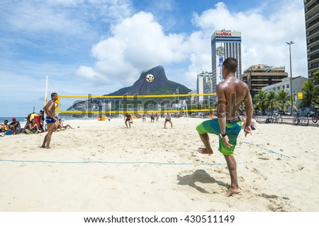 RIO DE JANEIRO - MARCH 17, 2016: Young Brazilian men play a game of futevolei (footvolley), a sport that combines football/soccer and volleyball, on the beach in Leblon.  - stock photo
