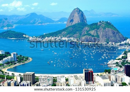 Rio de Janeiro, Olympic City 2016 - Sugar-loaf. Mountain resembling inverted funnel behind Urca hill. Tourist site in the former capital of Brazil.  Water around, and Niteroi city in the background. - stock photo
