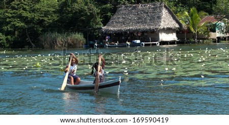 RIO DULCE, GUATEMALA -  DECEMBER 6: Children are rowing in a small boat near white lilies,at the arrival of tourists to sell them home made presents on December 6, 2013, in Rio Dulce, Guatemala.  - stock photo