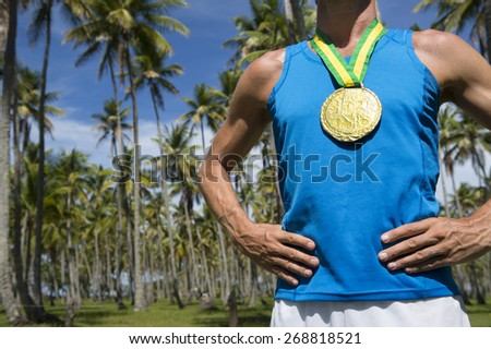 Rio 2016 first place athlete wearing gold medal standing outdoors with hands on hips in grove of tropical palm trees in Brazil - stock photo