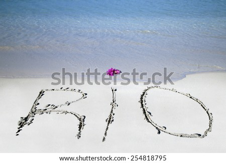 Rio written in the sand with red flower - stock photo