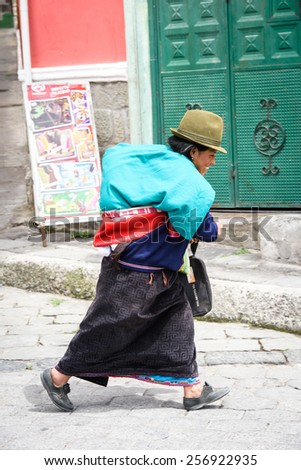 RIOBAMBA, ECUADOR - JAN 7, 2015: Unidentified Ecuadorian woman walks in traditional clothes and a bowler hat. 71,9% of Ecuadorian people belong to the Mestizo ethnic group