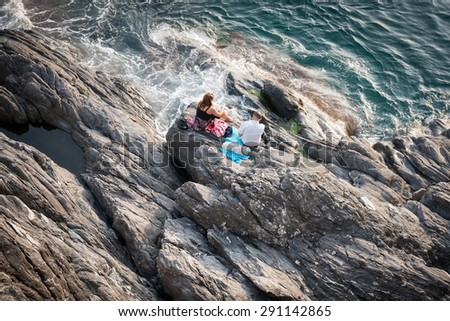 RIOMAGGIORE, ITALY- APRIL 25;Couple sitting relaxing on rugs on rocks looking out to sea enjoying a warm afternoon picnic with small dog on Mediterranean coast, April 23,2015 in Riomaggiore, Italy. - stock photo