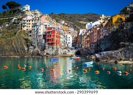 Riomaggiore, Liguria, Italy. The beautyful village of Riomaggiore as you can see it from the see, vith colorful houses reflecting themselves in the water. Blue sky.