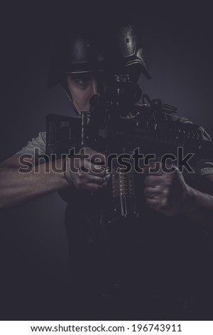 Riot, paintball sport player wearing protective helmet aiming pistol ,black armor and machine gun - stock photo