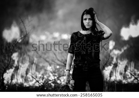 Riots, terrorism, aggression, violence, arson, mayhem,protest concept.Disaster in bush forest with fire spreading in dry woods caused by pyromaniac.Vandal makes fire.Grain added,toned image - stock photo