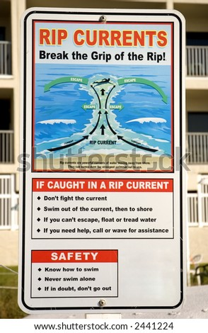 Rip current warning sign with beach front condos in background