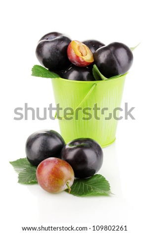 Rip plums in pail isolated on white