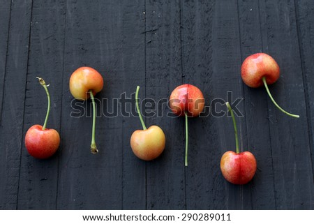 Ripe and fresh cherries on black background - still life - stock photo