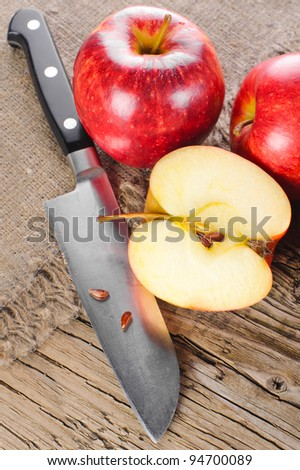 Ripe apple fruits and knife at old wooden table with canvas - stock photo
