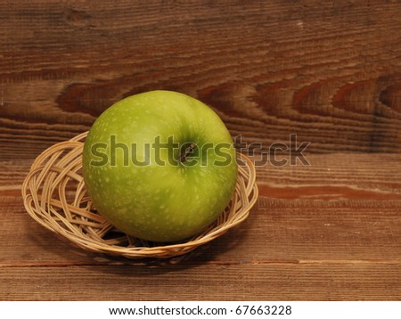 ripe apple in basket on wood background - stock photo
