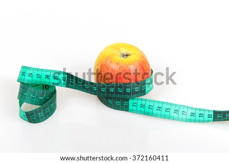 Ripe apple with a meter on a white background, weight loss concept, the principles of the diet, fat burners apples, conditions of purchase slim figure - stock photo