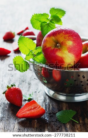 ripe apples and strawberries on old wooden table. fresh fruit from the garden. health and diet food - stock photo