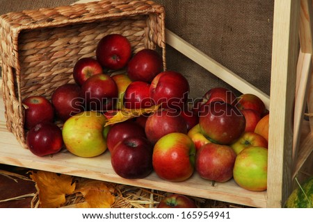 Ripe apples in basket on shelf close up