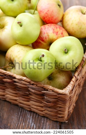 Ripe apples in basket on wooden table close-up - stock photo