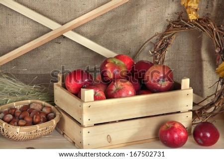 Ripe apples in crate with nuts and wreath of twigs on shelf on sackcloth background