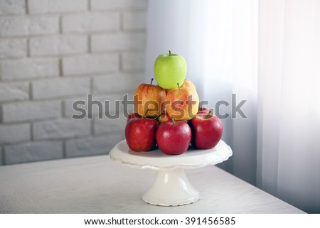 Ripe apples on stand on kitchen table - stock photo