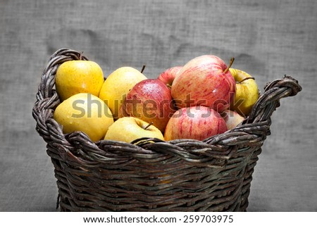 ripe apples on wicker basket with rustic background - stock photo