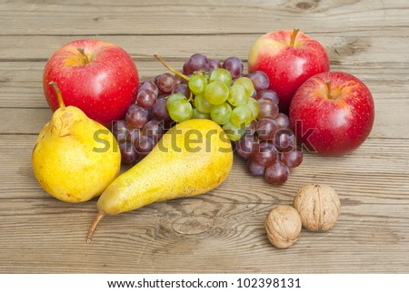 ripe apples, pears and grapes on rustic wooden table - stock photo