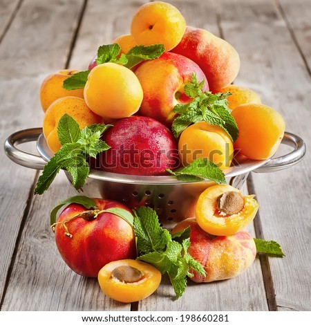 Ripe apricots, nectarines and saturn peaches in steel colander. Selective focus. - stock photo