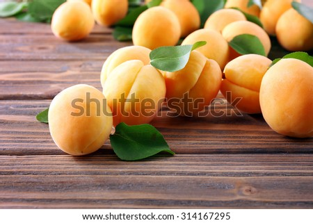 Ripe apricots on wooden table, closeup - stock photo
